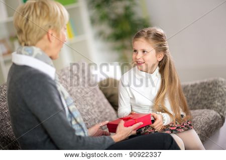 Cute girl giving her grandmother a gift, concept grandmother day