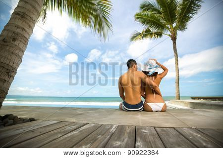 Love couple in tropical resort sitting on sea cost and looking at sea, back view