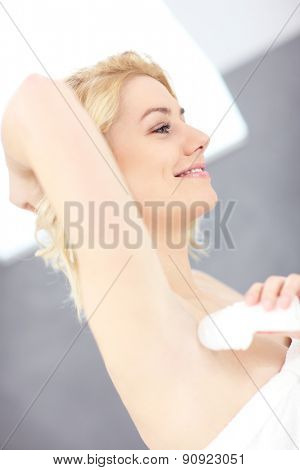 Woman using deodorant in the bathroom