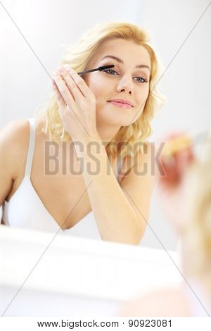 A picture of a young woman applying mascara in the bathroom