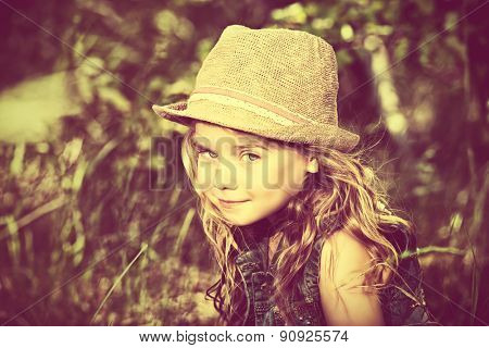 Close-up portrait of a cute curly girl in straw hat outdoor. Summer holiday. Vintage style.