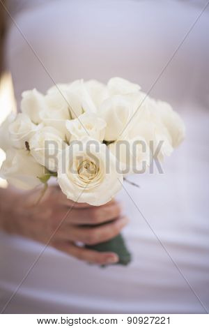 Bride In White Wedding Dress Holding Bouquet Of Rose Flowers