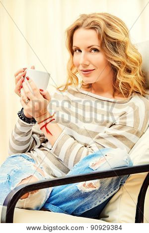 Beautiful young woman resting at home in a cozy armchair with a cup of tea. Interior.