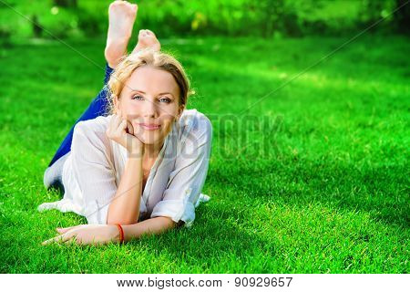 Beautiful happy woman lying on a grass outdoor and smilng.