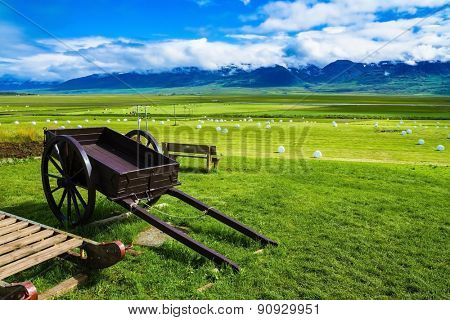 The reconstituted village -  Museum Vikings in Iceland. Old wooden sledge and two-wheeled cart on the lawn