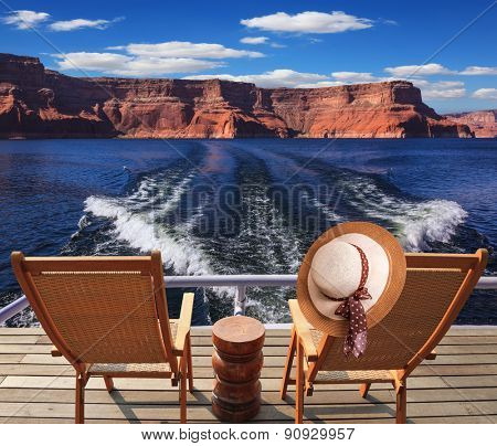 Waves from the boat cut through the Lake Powell. At the stern of the vessel are two deck chairs. On the back of one hanging elegant ladies straw hat.