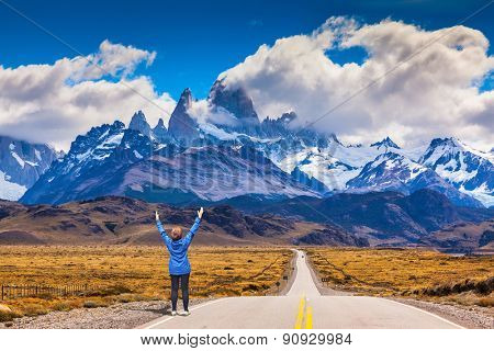 Woman delighted natural beauty raised her hands. The highway leads to the snow-capped peaks of Mount Fitzroy