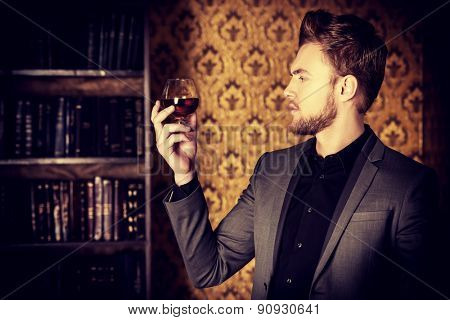Elegant man in a suit with glass of beverage and cigar in vintage room. Fashion.