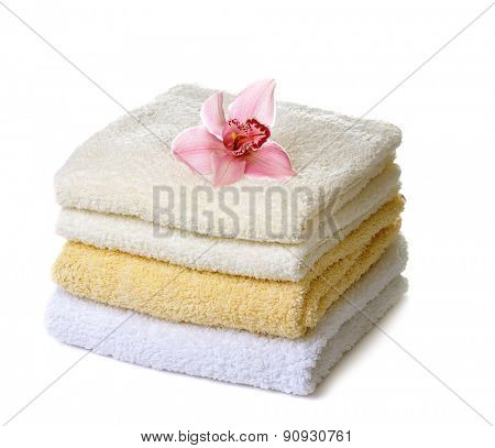 stack of  towels with pink orchid flower isolated on white