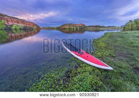 dusk over calm lake with a red stand up paddleborad  with a paddle on shore - Horsetooth Reservoir, Fort Collins, Colorado