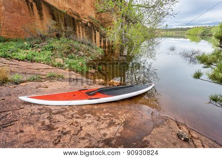 red stand up paddleboard  with a paddle on rocky lake shore - Horsetooth Reservoir, Fort Collins, Colorado