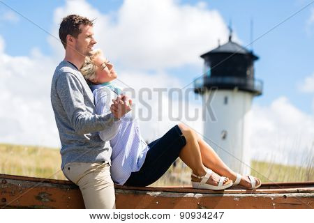 Couple having romantic vacation in German north sea beach dune in front of lighthouse