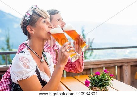 Couple on mountain hut drinking wheat beer, in the background alpine scenery