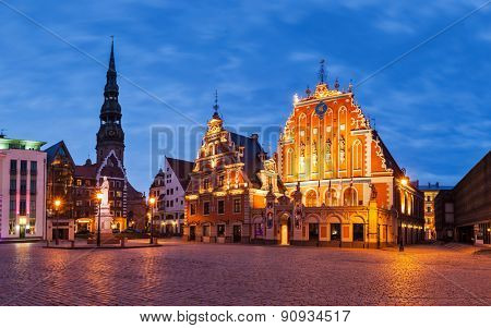 Panorama of Riga Town Hall Square with House of the Blackheads, St. Roland Statue and St. Peter's Church illuminated in the evening, Riga, Latvia