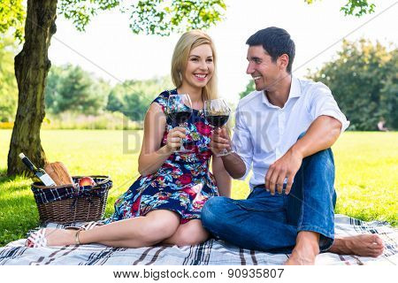 Couple having picnic wit red wine on meadow sitting on blanket with basket