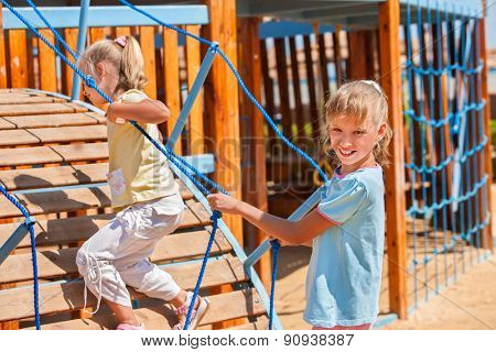 Happy two female children move out to slide in playground.
