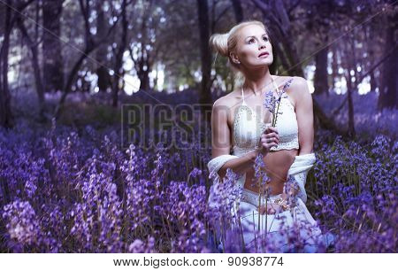 Artistic portrait of a blonde woman in a bluebell forest