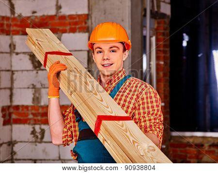 Happy man in builder helmet carry boards indoor.