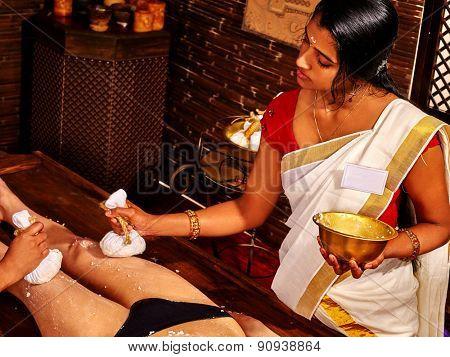 Young woman having indian feet Ayurveda spa massage.