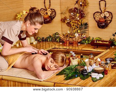 Young blond beautiful woman getting massage in bamboo spa.
