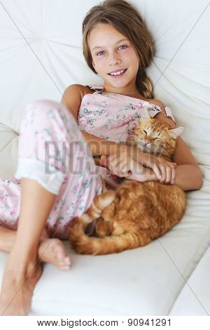 Preteen school girl of 8-9 years old with her pet resting on a sofa at home