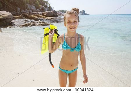 Preteen child posing with snorkeling equipment on a tropical beach