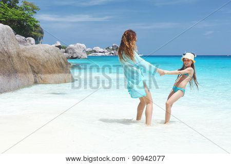 Mother playing with her 8 years old daughter on a tropical beach during summer vacations