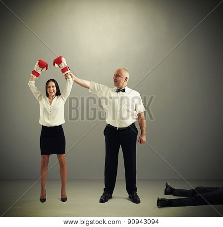 referee holding winner businesswoman in boxer gloves and looking at her, near lying knocked out businessman over dark grey background