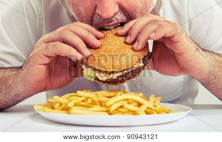 close up photo of man eating burger and french fries