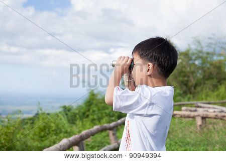 Little Child Look In Binoculars Outdoor In Sunny Summer Day