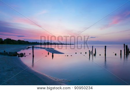 Old broken pier at sunset on the coast of the Baltic sea, Latvia