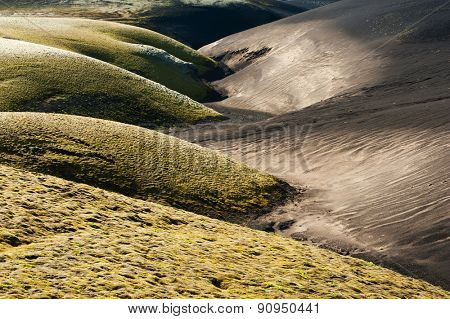 A contrasty wavy landscape of a former brook where black volcanic dunes meet green dunes covered by moss. Lakagigar volcanic area, Iceland. Sunset time