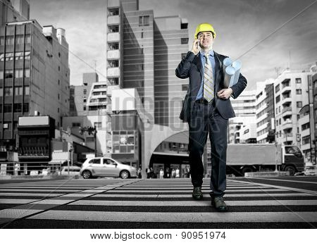 Architect in protective helmet speaking by phone on the crossroad