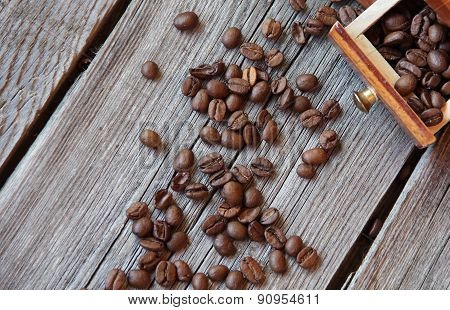 Coffee Grains And Manual Mill On A Wooden Table