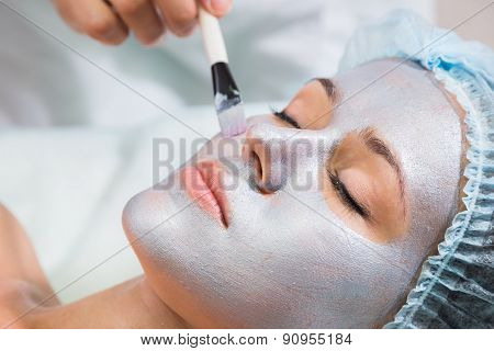 Girl with a beautician at spa salon. Beautician performs cosmetic procedures