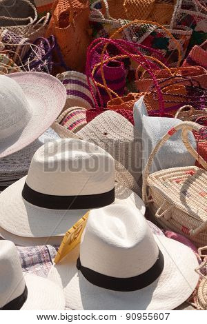 Straw hats and colorful sewn handbags in a beach market, Pedernales, Ecuador