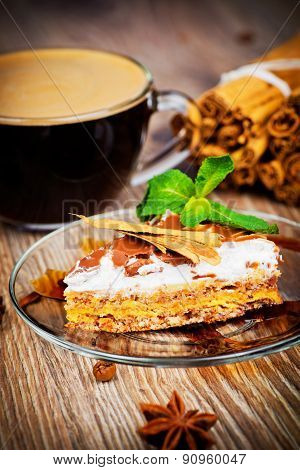 Cup of coffee and a cake on wooden background
