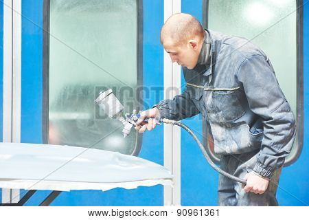 auto mechanic worker priming a car bonnet before painting in a chamber during repair work