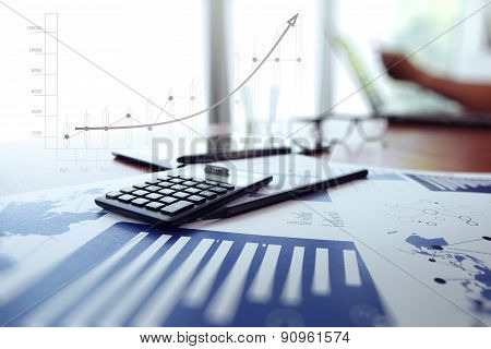 Business Documents On Office Table With Digital Tablet And Man Working With Smart Phone In The Backg