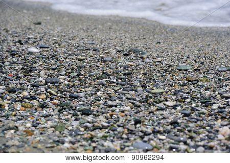 Sea multicolored pebbles, gravel beach in sunlight, selective focus, background