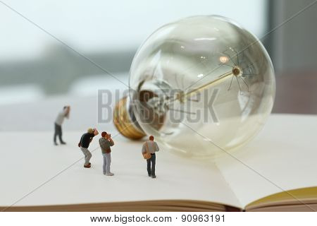 Creative Idea Concept - Miniature Photographer With Vintage Light Bulb On Open Paper Notebook