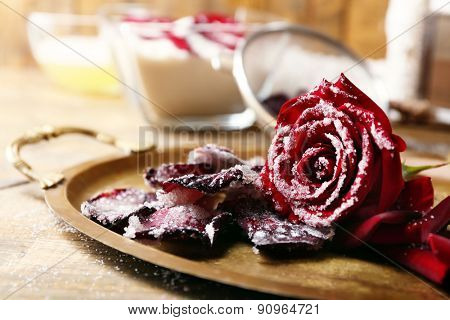 Making candied rose flower petals with egg whites and sugar, on wooden background