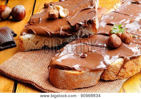 Bread With Chocolate Cream And Hazelnuts On A Wooden Table