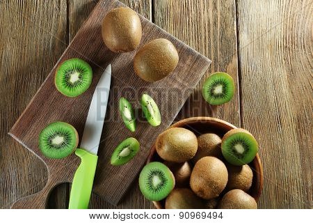 Juicy kiwi fruit with knife on cutting board on wooden background