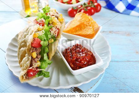 Tasty taco with nachos chips and tomato dip on table close up