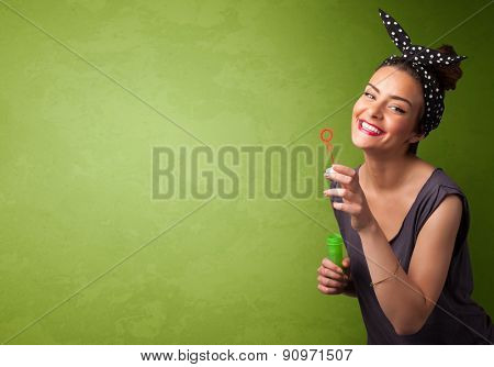 Beautiful woman blowing soap bubble on copyspace green background