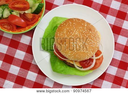 Cheeseburger with green salad shot from the top on red and white checkered cloth