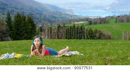 A Pretty Young Girl Listening To Music With Headphones