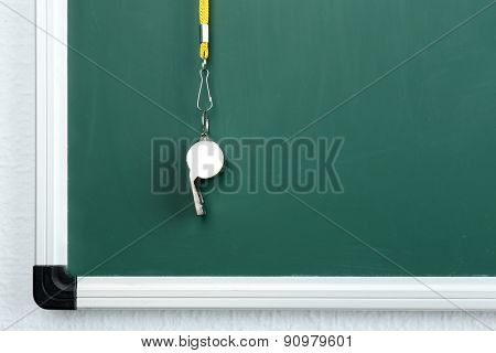 Whistle on blackboard background
