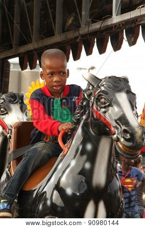Black African Boy Riding On Electronic Horse